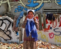 A woman holding a photo of Ny Sokha in a neighborhood filled with street art